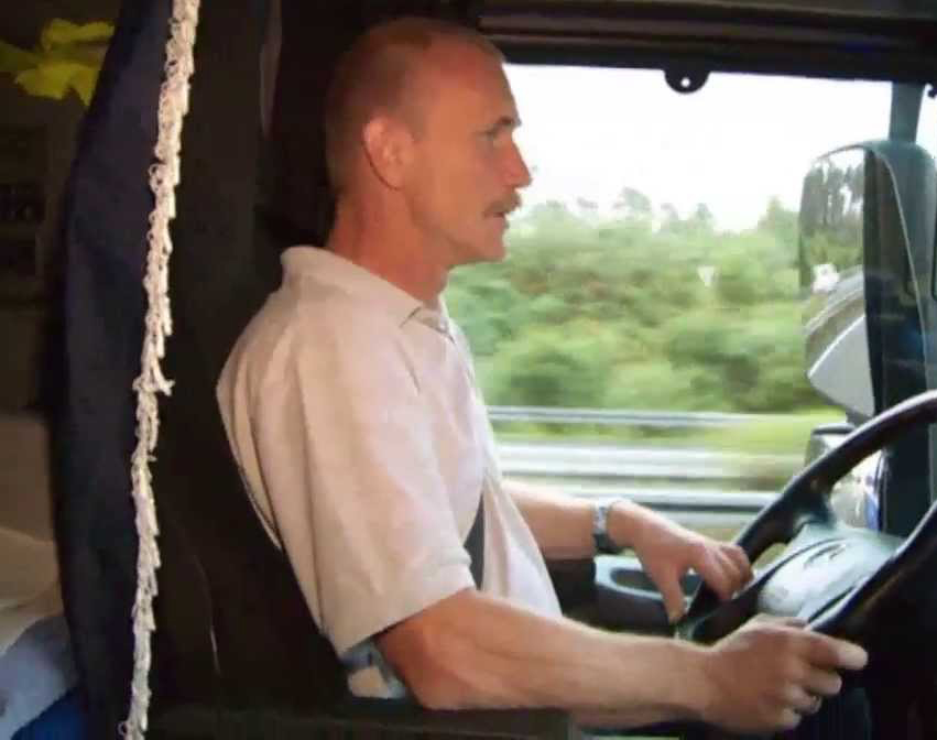 Дальнобойщик сидит за рулем грузовика и выполняет задание в рейсе