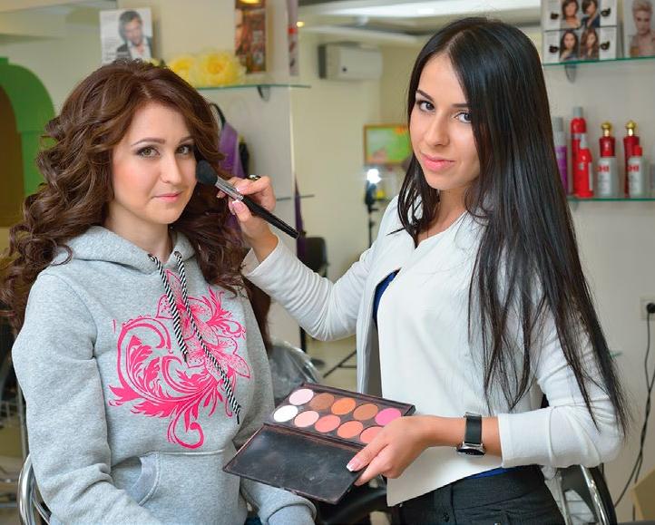 Девушка-визажист работает со своим клиентом.