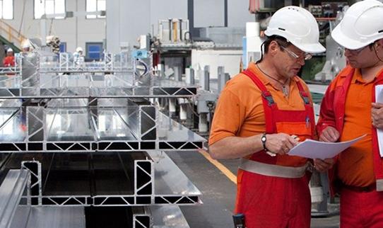 Процесс производства алюминиевого профиля в цеху двумя работниками.
