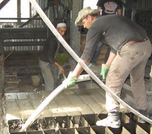 Заливка пеноботона в формы на заводе двумя работниками.