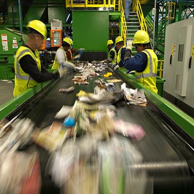 Сотрудники завода сортируют мусор до переработки.