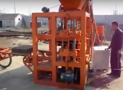Процесс изготовления шлакоблоков на оборудовании работниками.
