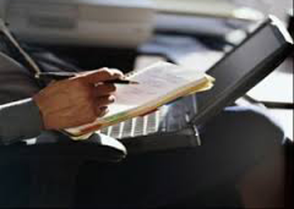 Мужчина пишет статью за ноутбуком.