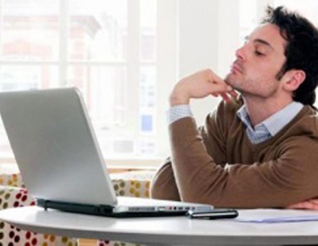 Копирайтер сидит за ноутбуком и зарабатывает написанием статей.