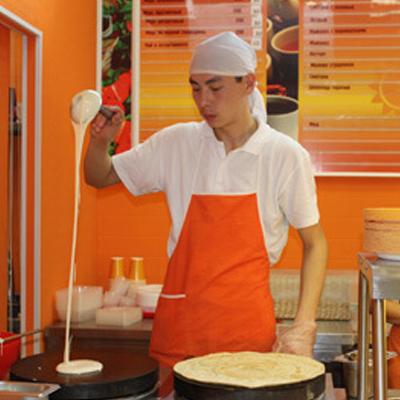 Повар готовит блины на открытой кухне заведения .