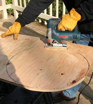 Мастер с помощью автоматической ленточной пилы вырезает из фанеры крышку для бочки.