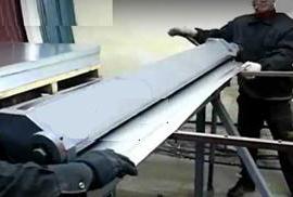 Процесс производства профнастила двумя работниками на установке.