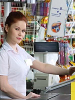 Девушка касир стоит за прилавком в продуктовом магазине.