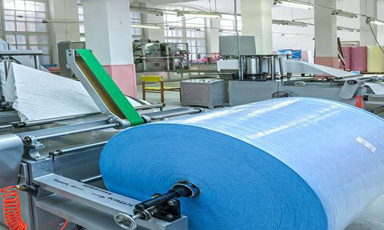 Оборудование высокой технологичности для производства спанбонда в цеховом здании.