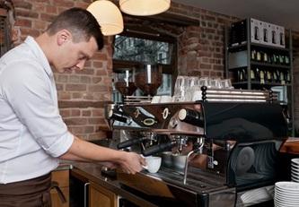Бариста готовит кофе в кафетерии.