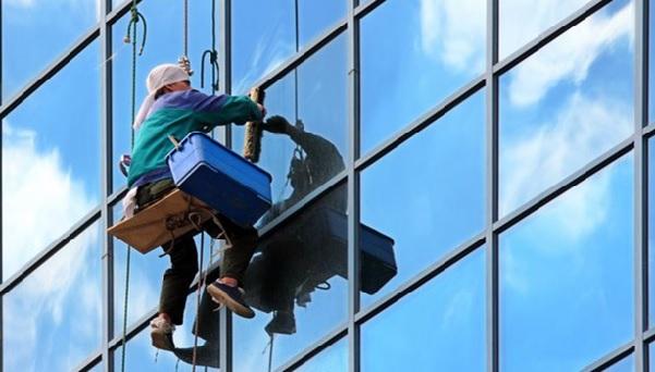 Альпинист моет окна на высоте.